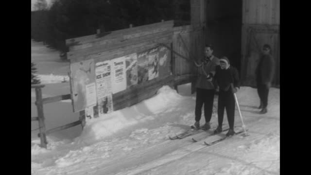 vídeos de stock, filmes e b-roll de vs model couple attempts to get on tbar ski lift with retakes and several falls pam wears a geny spielmann jacket with sheepskin trim / scene counter... - 1950