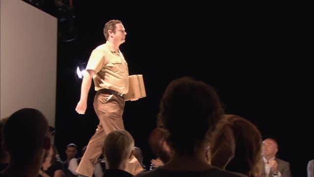 ms model dressed as delivery man walking onto catwalk as people clap/ model posing with cardboard box/ london, england - この撮影のクリップをもっと見る 1064点の映像素材/bロール