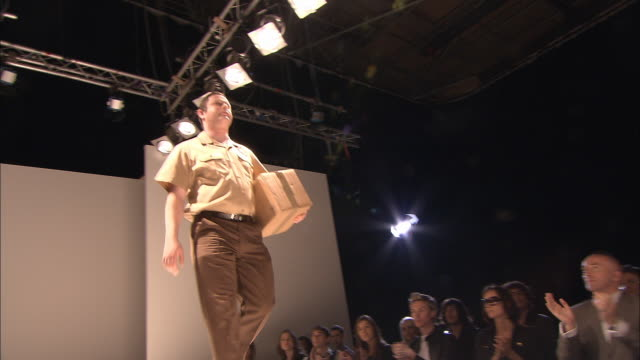 ms model dressed as delivery man walking onto catwalk as people clap/ london, england - admiration stock videos and b-roll footage