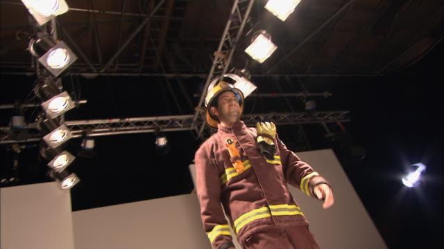 la ms  model dressed as fireman walking onto catwalk as people clap/ london, england - laufsteg stock-videos und b-roll-filmmaterial