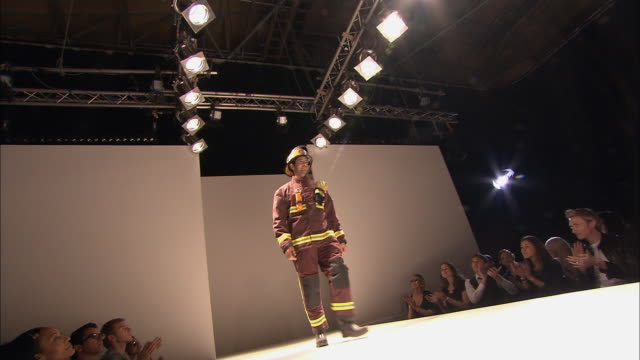 la ws model dressed as fireman walking onto catwalk, turning around, and leaving as people clap/ london, england - out of context stock videos & royalty-free footage