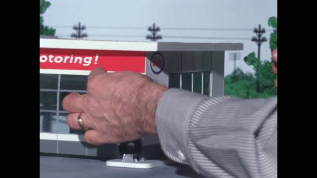 "model gas station, giant hands install ""happy motoring"" sign - table top shot stock videos & royalty-free footage"