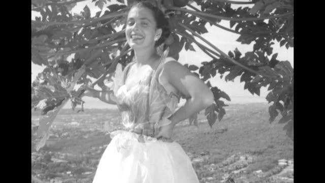 model ginny, standing under tree, models pauline lake flouncy skirt and leaf motif halter top on hill overlooking honolulu / ginny, on beach, models... - strapless stock videos & royalty-free footage