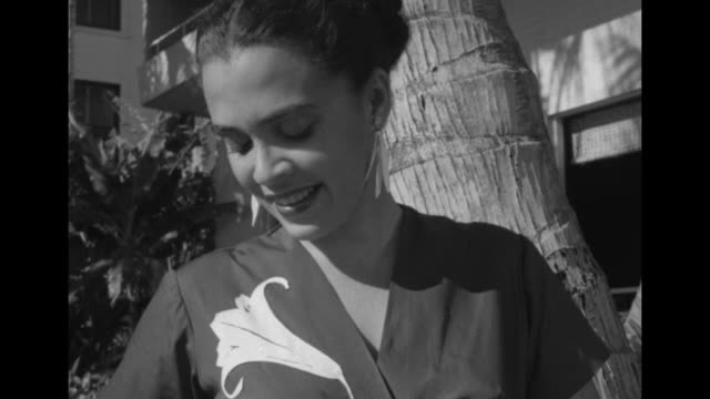Model Ginny stands under a palm tree on the beach strumming a ukulele she wears Pauline Lake fashions a silk wraparound blouse a skirt with Hawaiian...