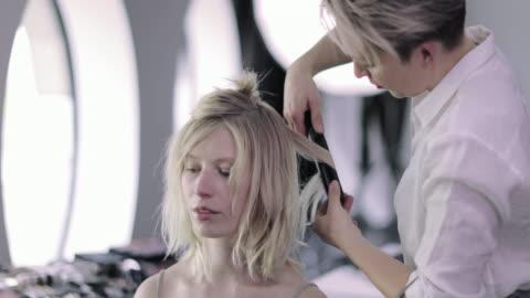 model having hair styled on a photoshoot - sfilata di moda video stock e b–roll