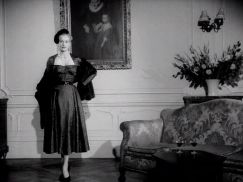 vidéos et rushes de a model in a formal looking room unwraps her fur stole to show off her dress 1953 - châle
