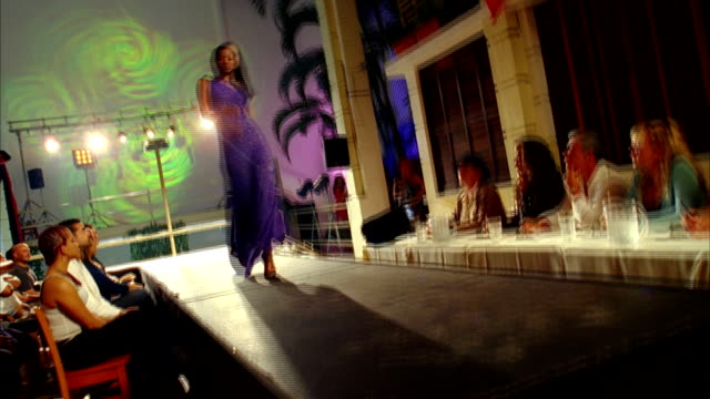 A model in a purple dress struts up and down a runway. Available in HD.
