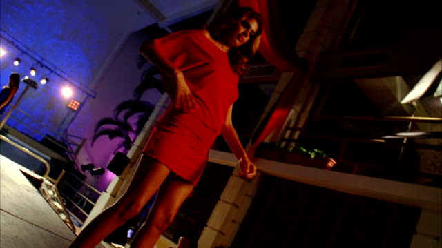 A model in a red dress struts down a runway. Available in HD.