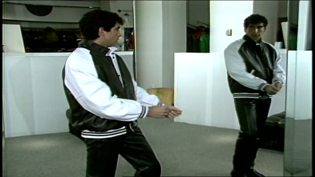 model in black and white leather varsity jacket looking into mirror - varsity jacket video stock e b–roll