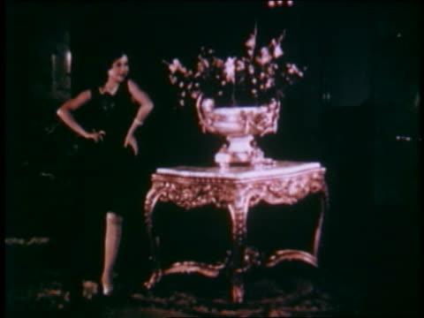 1929 model in black dress walking towards camera by elegant table / dissolve