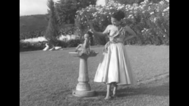 Model in oneshouldered cocktail dress top covered with anthurium standing at a fountain in Honolulu / Note exact day not known