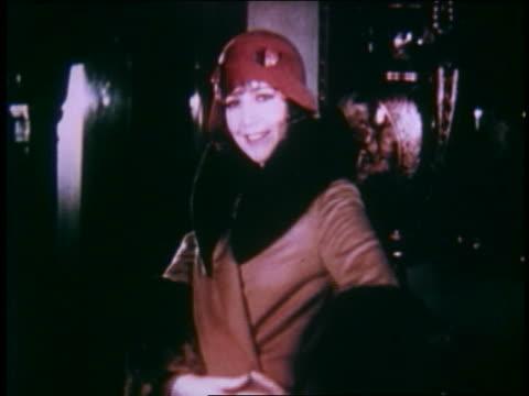 1929 model in red hat + fur-trimmed coat smiling + posing indoors - 毛皮のコート点の映像素材/bロール