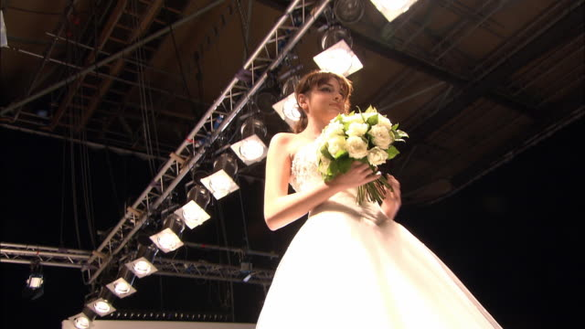 la ms pan model in strapless wedding dress holding flowers and walking on catwalk, turning around, and walking back/ london, england - strapless stock videos & royalty-free footage