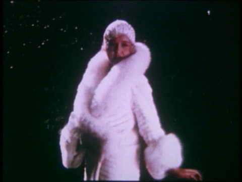 1929 model in white hat + fur-trimmed coat smiling + posing outdoors