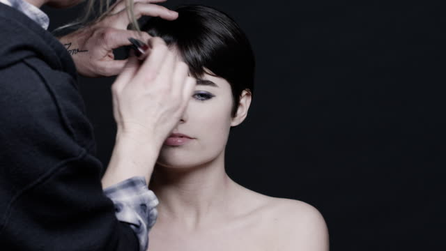 A model is adjusted by her stylist.