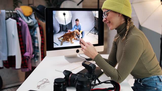 model schaut sich ihre fotos nach der foto-session an. er nutzt sein smartphone und tippt nachrichten - digitalkamera bildschirm stock-videos und b-roll-filmmaterial