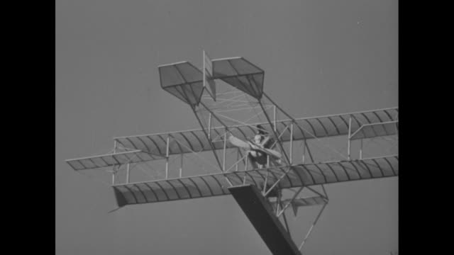 cu model of early seaplane rotates in air for camera / biplane flying boat lands next to ship in icy waters / men pull biplane through chunks of ice... - aerospace industry stock videos & royalty-free footage