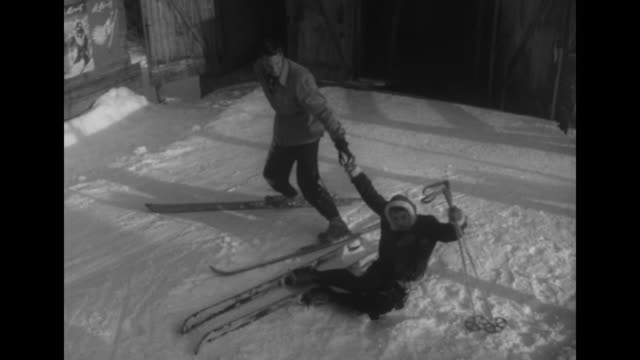 Model Pam laying in snow with skis wearing a Geny Spielmann jacket with sheepskin trim pretending to fall she mouths words which might be curses and...