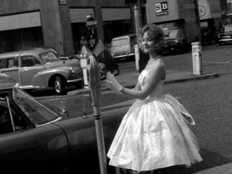 A model poses in a cocktail dress and gloves on a street