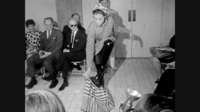 model poses in rudi gernreich fall outfit in front of audience / model pulls her skirt down / coat becomes mini dress / model in reversible coat /... - 自動車ブランド mini点の映像素材/bロール