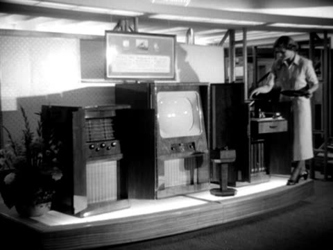 model poses next to a large television and record player unit at the national radio show at earls court. - earls court stock videos & royalty-free footage