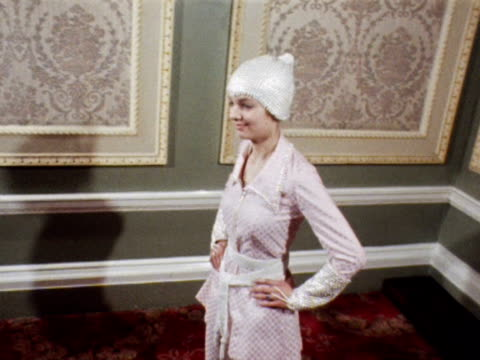 a model poses wearing a pink trouser suit with a pearl belt and cap 1969 - 1960 1969 video stock e b–roll