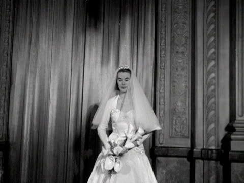a model poses while wearing a wedding dress with a diamond tiara and pearl necklace at a jewellery fashion 1952 - composizione di fiori video stock e b–roll