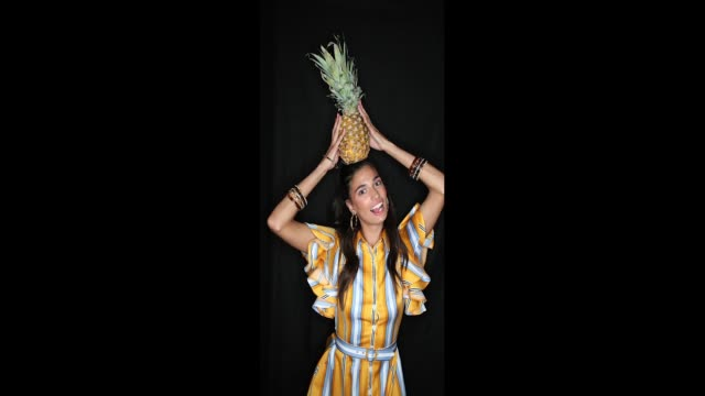 A model poses with a pineapple backstage ahead of the Lena Hoschek show during the Berlin Fashion Week Spring/Summer 2019 at ewerk on July 3 2018 in...