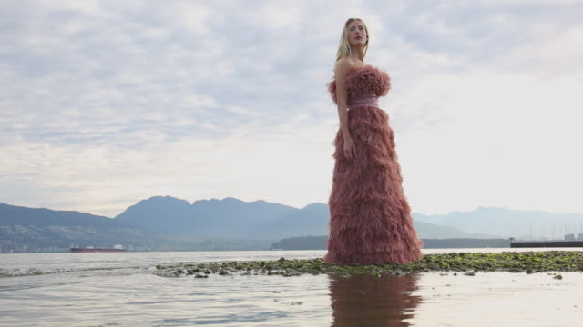 Model poses with feather dress, in ocean shallows