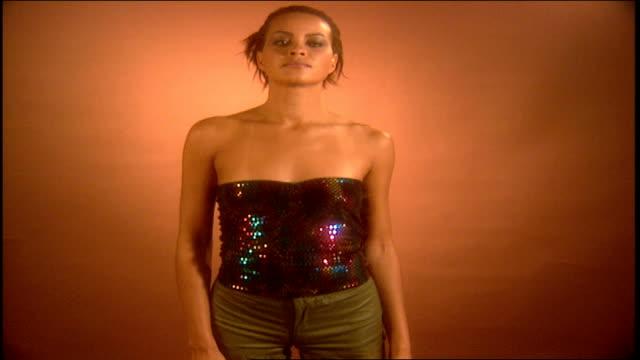 vídeos y material grabado en eventos de stock de model posing in multi colored sequins camisole and gold pants - camisola