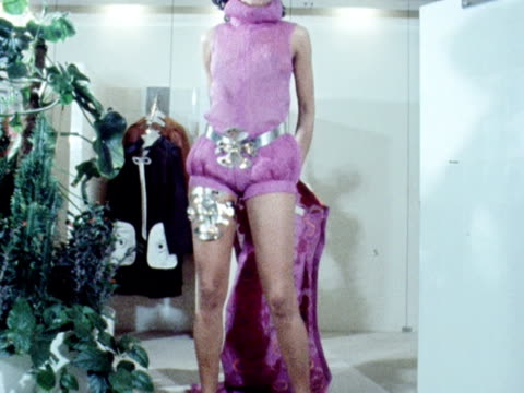 model removes a brightly patterned sleeveless coat to reveal purple shorts and a top with an elaborate metal garter and matching belt. 1970. - sleeveless top stock videos & royalty-free footage