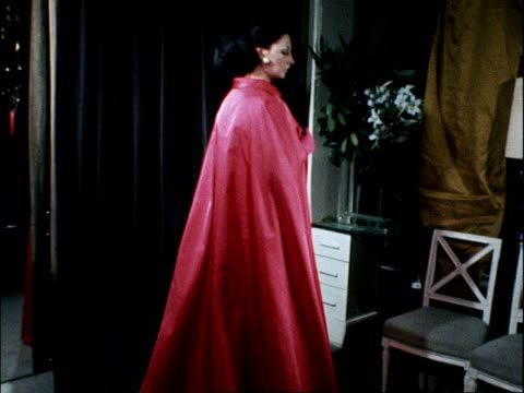 A model removes a pink silk cape to reveal a gold embroidered dress underneath designed by Norman Hartnell 1968