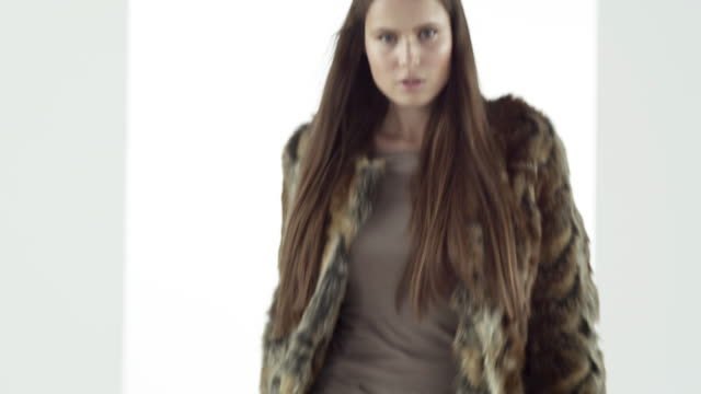 Model removing fur coat on catwalk at fashion show