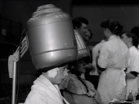 A model sits under a hairdryer during a hairdressing competition 1953