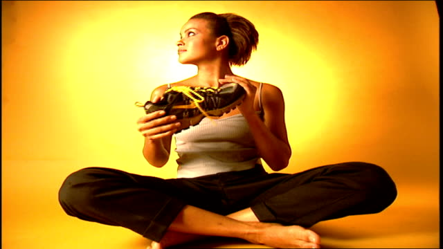 vídeos de stock e filmes b-roll de model sitting cross legged on floor holding black and yellow nike shoes - cross legged