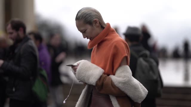 model soo joo park wears an orange turtleneck sleeveless vest a sheepskin jacket a brown leather fantasy belt a black bag white wideleg pants white... - turtleneck stock videos & royalty-free footage