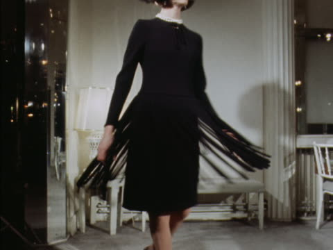 A model spins while wearing a black fringed cocktail dress designed by Norman Hartnell