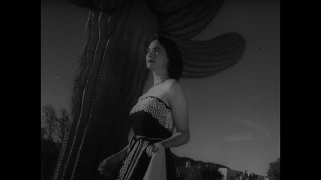Model standing next to saguaro cactus removes short patterned capelet from around her shoulders revealing matching garment around chest she poses...