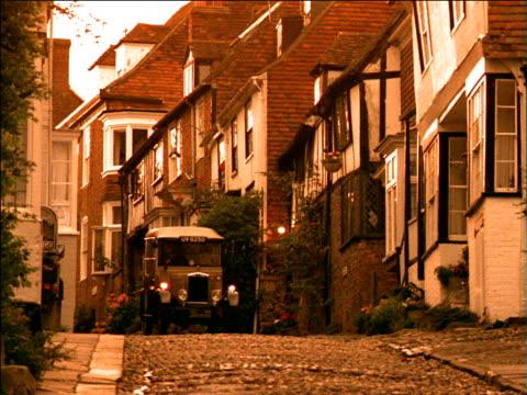 vidéos et rushes de model t ford car drives slowly down narrow cobbled street - ford model t
