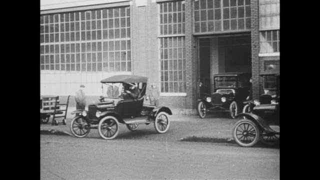 Model T Ford cars drive off the assembly line