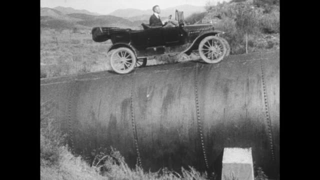 model t ford cars driving across train trellis and on top of giant culvert - model t stock videos and b-roll footage