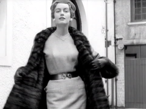 model takes off her fur coat to model her dress in a london street 1953 - pelliccia materiale tessile video stock e b–roll