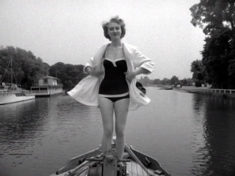 A model takes off her hooded jacket to reveal her swimsuit on a boat moving along the River Thames