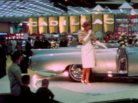 1965 model talking into microphone standing next to convertible in car show / Detroit / industrial