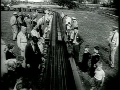 vidéos et rushes de model trains pass by / unger stands next to train / trains run on 335 foot track / children enjoy watching model trains / narrated - raconter