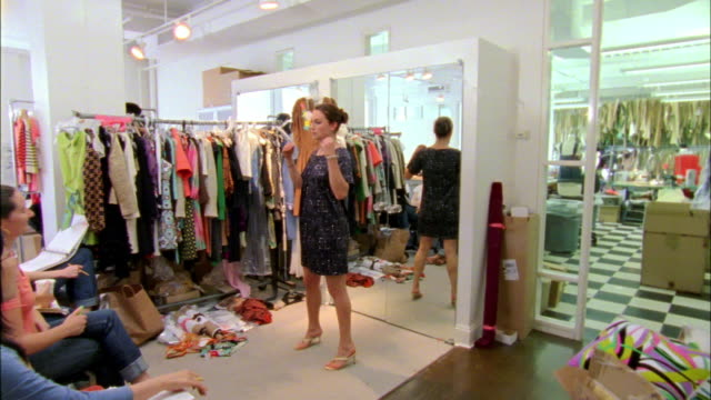 ws model trying on dress in designer's workshop, new york city, new york, usa - anpassen stock-videos und b-roll-filmmaterial