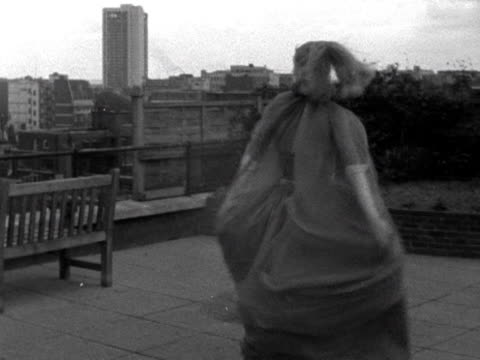 A model twirls around whilst wearing a chiffon evening gown and cape on a London rooftop garden 1963