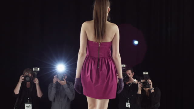model walking on catwalk with photographers - kamera blitzlicht stock-videos und b-roll-filmmaterial
