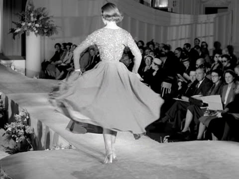 A model walks down a catwalk wearing a cocktail dress at a fashion show 1954