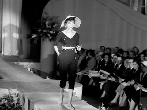 a model walks down a catwalk wearing a jersey play suit and a straw hat 1953 - straw hat stock videos & royalty-free footage